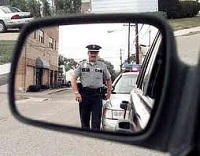 Police Officer in Sideview Mirror - Boulder Criminal Defense Attorney