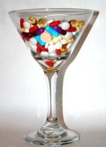Martini glass full of different pills on a white background