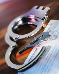 Handcuffs with key on a wooden table with paper work