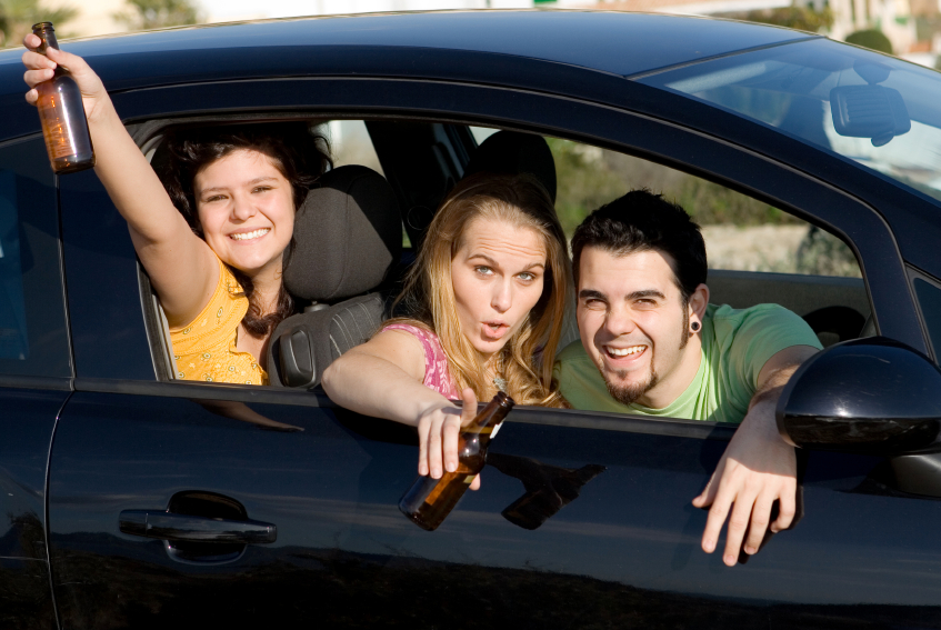Three younger adults in drinking in a car