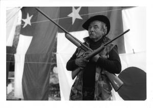 Man carrying two rifles in front of flags.
