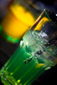 image of a green cocktail and a yellow cocktail in glasses with straws