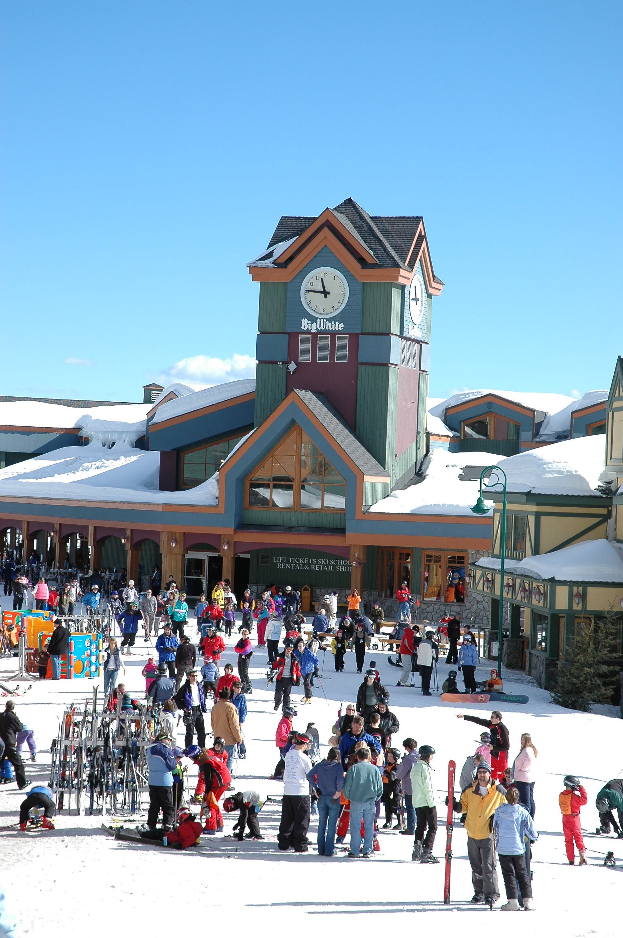 Clock tower at a ski resort with skiers all around