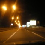 View of the road from the windshield of a car at night with street lights