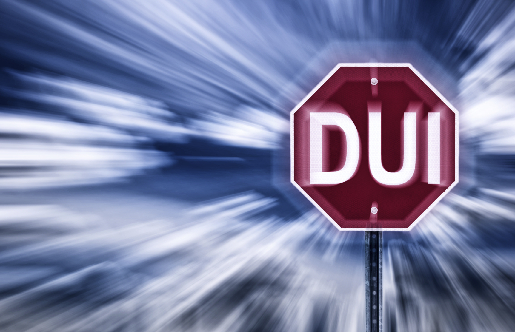 "Red stop sign with the letters ""DUI"" on it on a blue blurry background"