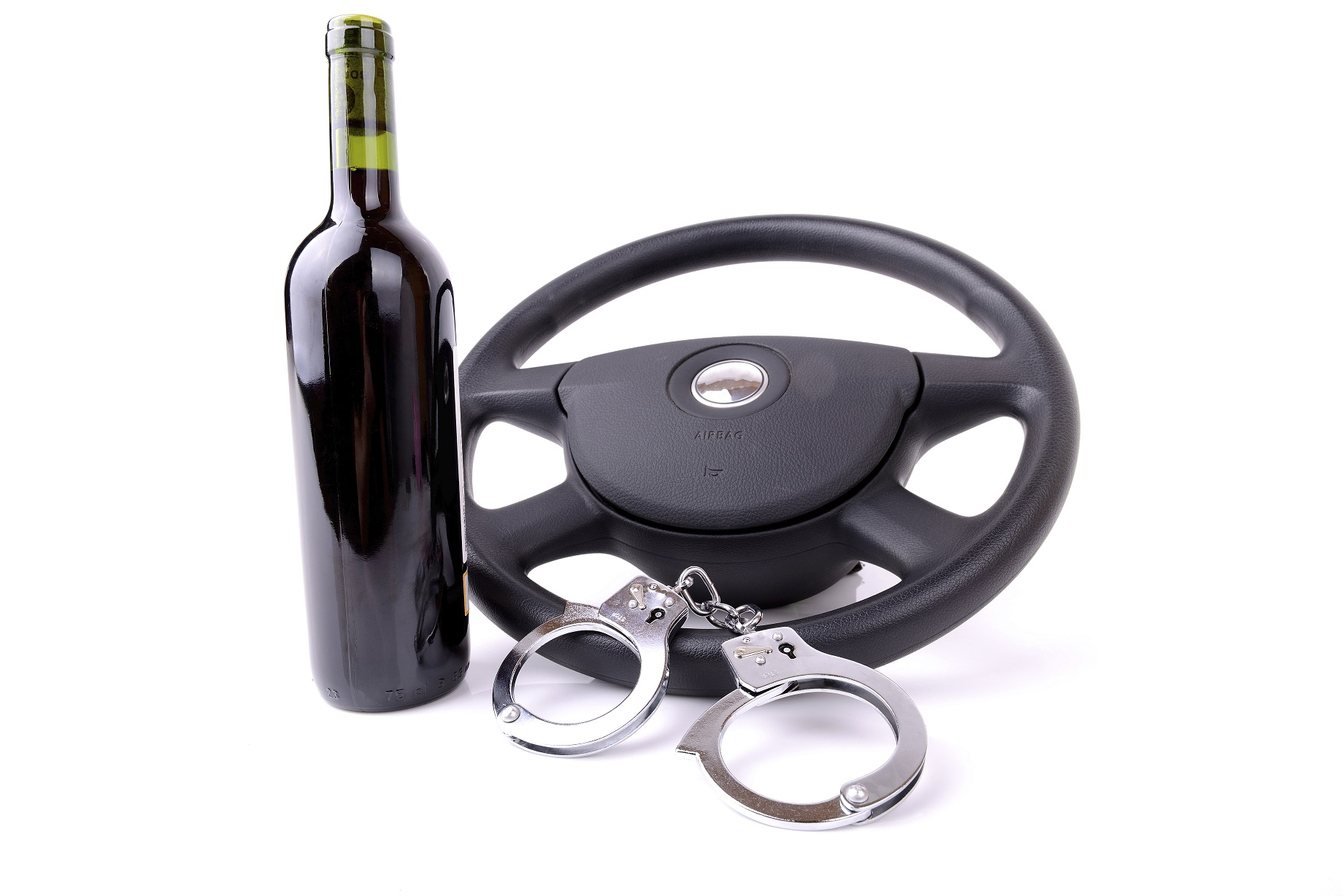 Wine bottle, steering wheel and metal handcuffs on a white background