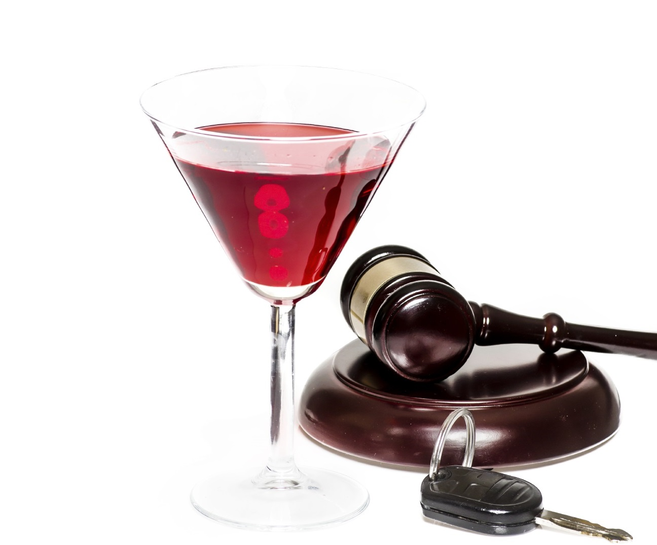 Martini glass with red liquid, gavel and car keys on a white background